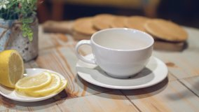 Tea being poured into white tea cup. Dessert and hot drink. Lemon slices. Tea time. Slow motion.  Breakfast concept.