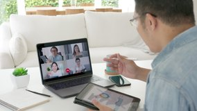 Zoom out the back view. businessman talking in a video conference.Asian team using laptop and tablet online meetings in a video calls.Working from home, Working remotely and Self isolation at home