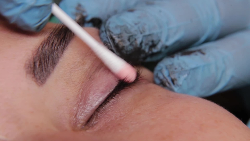 beautician is using small cotton swab for remove dye from eyelids of female client in a beauty salon. Royalty-Free Stock Footage #1057377898