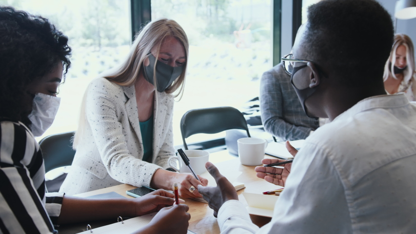 Office workplace with COVID-19 safety. Young multiethnic business people meeting at work wearing multi-use face masks. Royalty-Free Stock Footage #1057378126