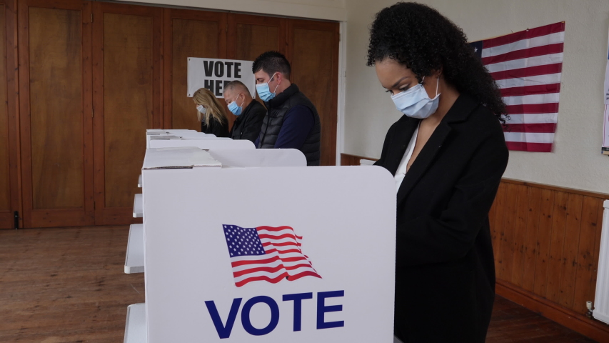 4K: Voters voting at Polling Place of the USA Election.  Diverse People Stood at booths wear Face Masks. Gimbal shot. Stock Video Clip Footage Royalty-Free Stock Footage #1057379191