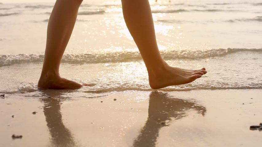 Person walking on the beach at sunset during summer vacation holidays slow-motion, closeup of legs and feet in the sea water, dolly video | Shutterstock HD Video #1057380787