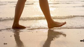 Person walking on the beach at sunset during summer vacation holidays slow-motion, closeup of legs and feet in the sea water, dolly video
