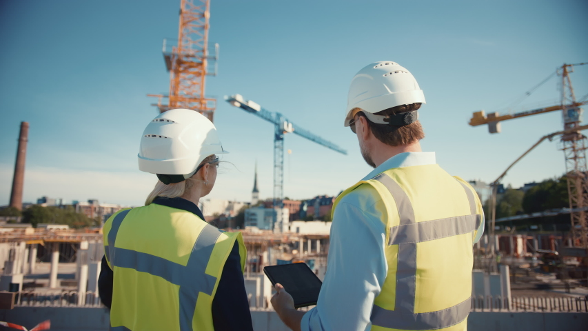 Male Civil Engineer and Young Female Building Architect Use a Tablet Computer on a City Construction Site. They Talk About the Future of Real Estate Development and Planning. Wearing Safety Hard Hats. Royalty-Free Stock Footage #1057388116