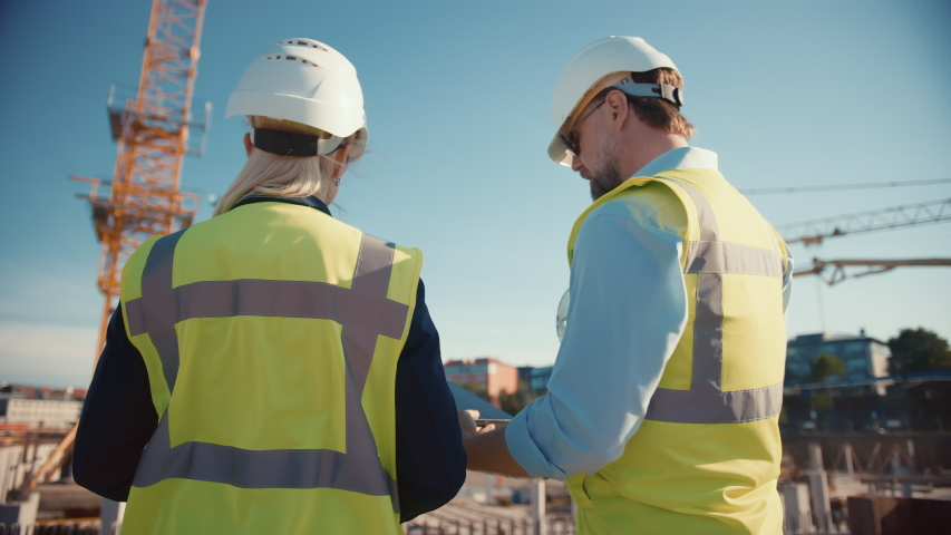 Male Civil Engineer and Young Female Building Architect Use a Tablet Computer on a City Construction Site. They Talk About the Future of Real Estate Development and Planning. Wearing Safety Hard Hats. Royalty-Free Stock Footage #1057388119