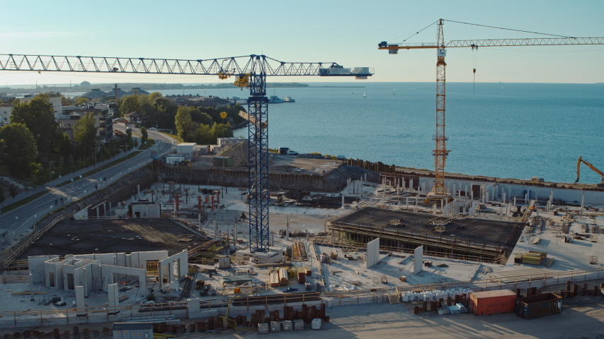 Aerial Flight Over a New Constructions Development Site with High Tower Cranes Building Real Estate. Heavy Machinery and Construction Workers are Employed. Blue Sea and City Houses in the Background. Royalty-Free Stock Footage #1057388167