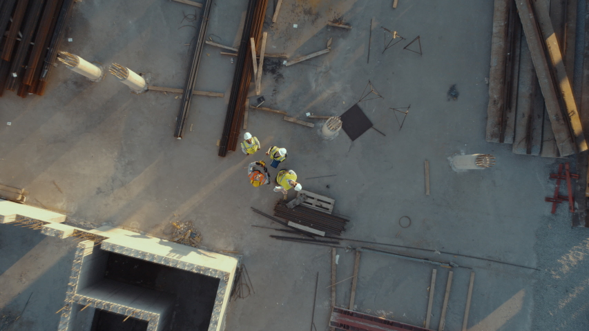 Aerial Top Down View on a Constructions Site with Diverse Team of Engineers and Worker with Theodolite Looking Up and Smiling. Heavy Machinery and Construction Workers are Working in the Area.
