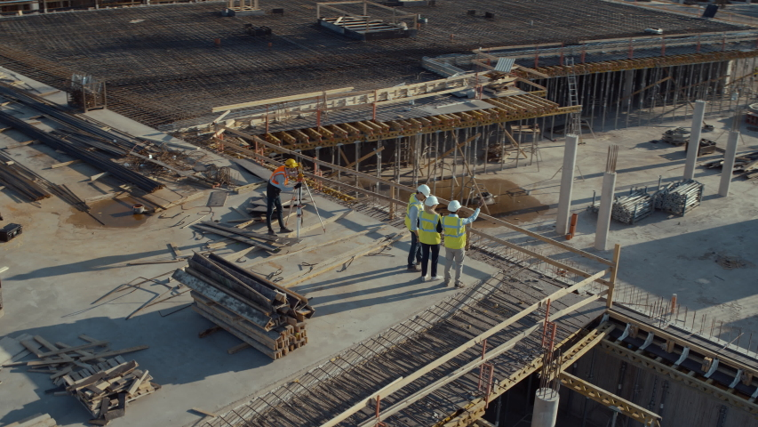Aerial Flight Over a New Constructions Development Site with Diverse team of Engineers and Architects Discussing Real Estate Projects. Heavy Machinery and Construction Workers are Working in the Area.