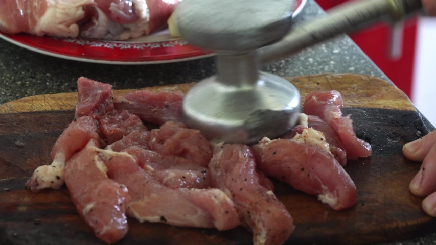 Woman hand tenderize raw meat, top view. Cooking and preparing meat on wooden cutting board. | Shutterstock HD Video #1057390846