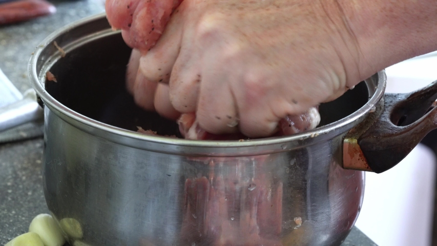 Woman crush raw meat in a saucepan. Cooking and preparing meat on wooden cutting board. | Shutterstock HD Video #1057390849