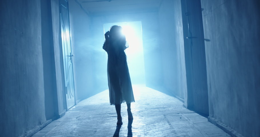 Little caucasian girl in ghost white sundress stretching her arms into camera while walking in hallway of haunted house, frightening someone 4k footage   Shutterstock HD Video #1057391440