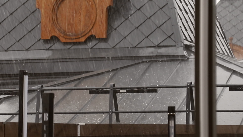 Hail falls on the roof of a house during a thunderstorm. Roof damage from hail. The hail hit the roof of the house. Roof damage from a thunderstorm | Shutterstock HD Video #1057391599
