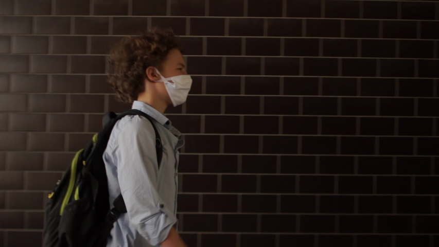 Curly-haired schoolboy in a medical protective mask goes to school. A boy in a blue shirt carries a backpack behind his back, a child walks along an underground passage. Back to school covid Royalty-Free Stock Footage #1057395394