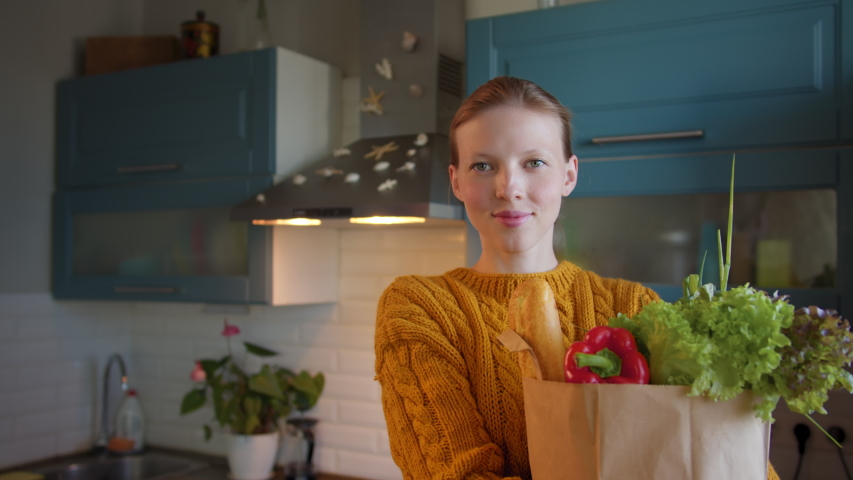Young beautiful woman with groceries bag in hands at kitchen looks camera smiling and happy. Home delivery products. Buying fresh food, conscious consumption Royalty-Free Stock Footage #1057395625