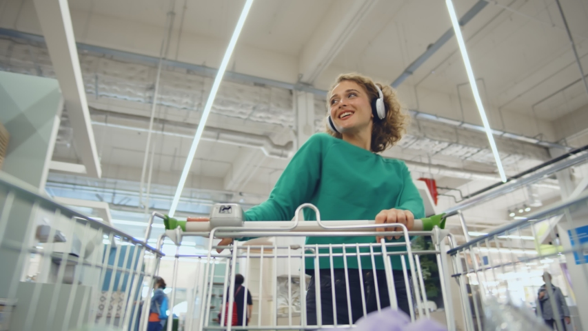 Low angle view of cheerful girl in headphones shopping in house improvement store. Young happy woman pushing trolley walking in home decoration store #1057397239