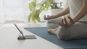 hand of woman Practicing yoga online with Trainer  learning  tablet on yoga mat  at home morning and sunlight, Concept of relaxation and meditation