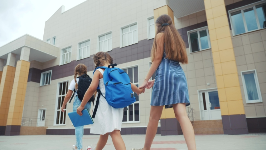 Parent leads to school child with backpack back view. kids go to school with backpacks education concept. mom leads daughter lifestyle by hand to first lesson. group school girl children go to class | Shutterstock HD Video #1057398952