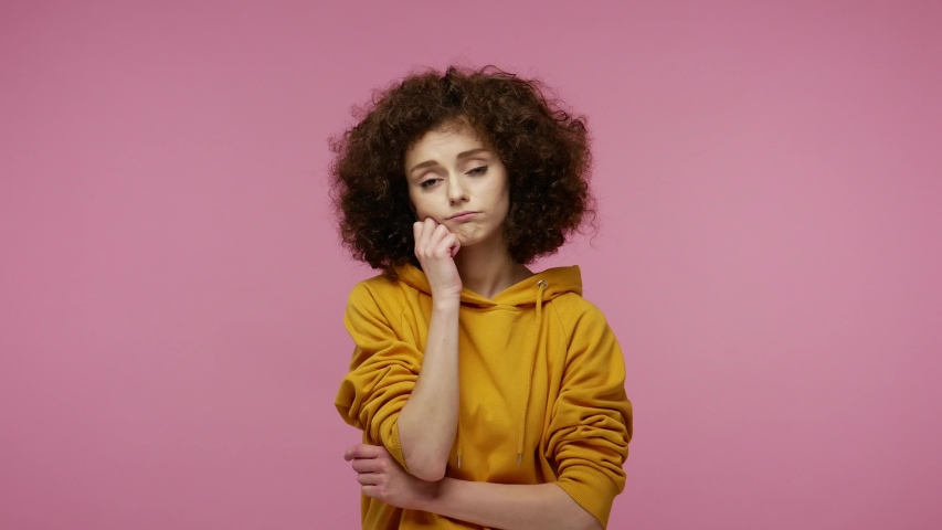 Lazy sleepy girl afro hairstyle in hoodie standing leaning on hand, looking at camera with bored indifferent expression, exhausted of tedious communication. studio shot isolated on pink background | Shutterstock HD Video #1057400623