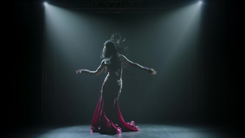 Young female belly dancer shaking her hips. Shot in a dark studio with smoke and neon lighting. Silhouettes of a slender flexible body. Slow motion. | Shutterstock HD Video #1057402060