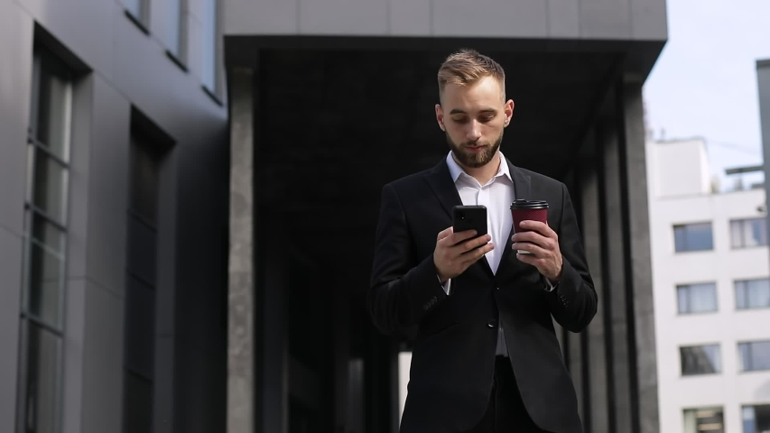 Bearded Handsome Man enjoying his Tasty Coffee. Typing Messages on his Smartphone and drinking hot beverage. Wearing stylish clothes. Having nice Hairstyle. | Shutterstock HD Video #1057402948