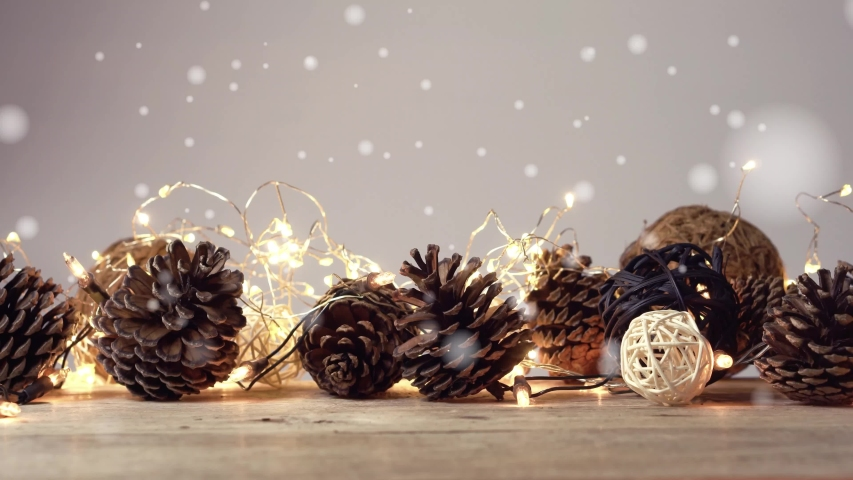 Snowflakes, Flashing lights and pine cone Christmas decoration on wooden table with copy space in vintage style for the celebration on Christmas Day or New Year concept background     Shutterstock HD Video #1057404808