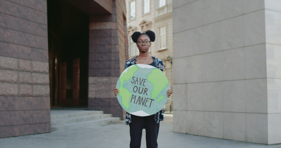 Afro american girl holding model of Earth with save our planet writing . Young serious woman fighting against environmental pollution at street. Concept of eco movement. Zoom in. | Shutterstock HD Video #1057404928