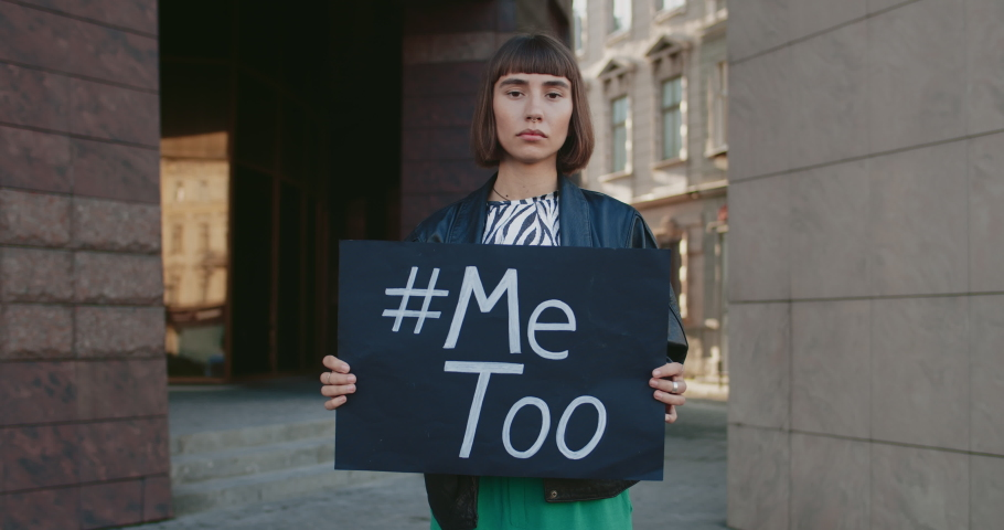 Portrait of young woman holding banner with MeToo writing and standing at city street. Girl with nose ring supporting movement against sexual harassment. Concept of social problems. | Shutterstock HD Video #1057404934