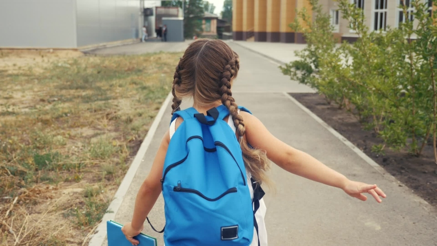 Little girl kid with a backpack and a textbook runs hurrying to school. education concept. little schoolgirl with a backpack runs to the school building. child running with textbook back fun view   Shutterstock HD Video #1057405030