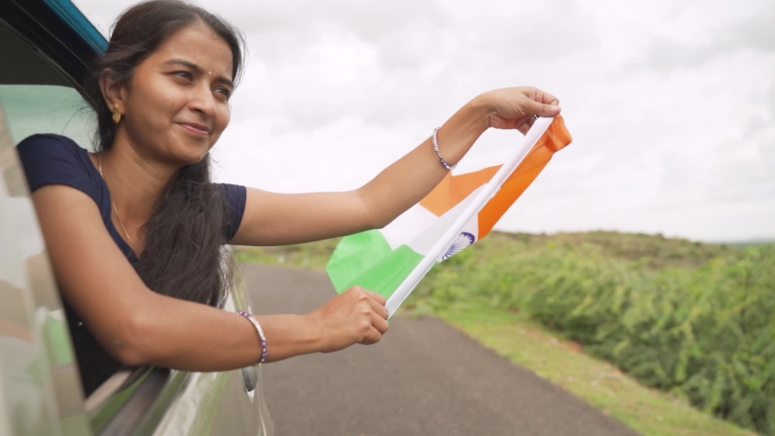 Happy Cheerful proud Young girl holding Indian flag from moving car window - Concept of patriotism and Independence or republic day celebration. | Shutterstock HD Video #1057405075
