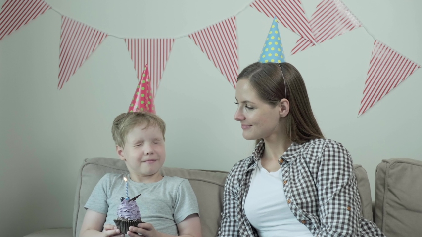 A boy makes a wish and blows out a candle on a birthday cupcake. Child dreaming. | Shutterstock HD Video #1057405081