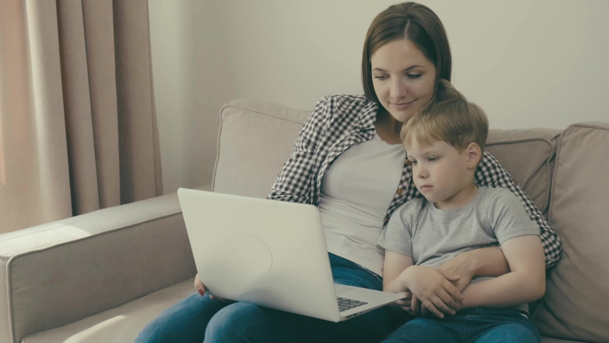 A young mother and child are watching an educational film or cartoon together. | Shutterstock HD Video #1057405096