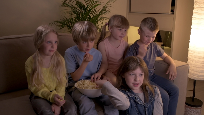 Five lovely children watch cartoon on TV at night, rejoice, laugh and have fun. | Shutterstock HD Video #1057405123