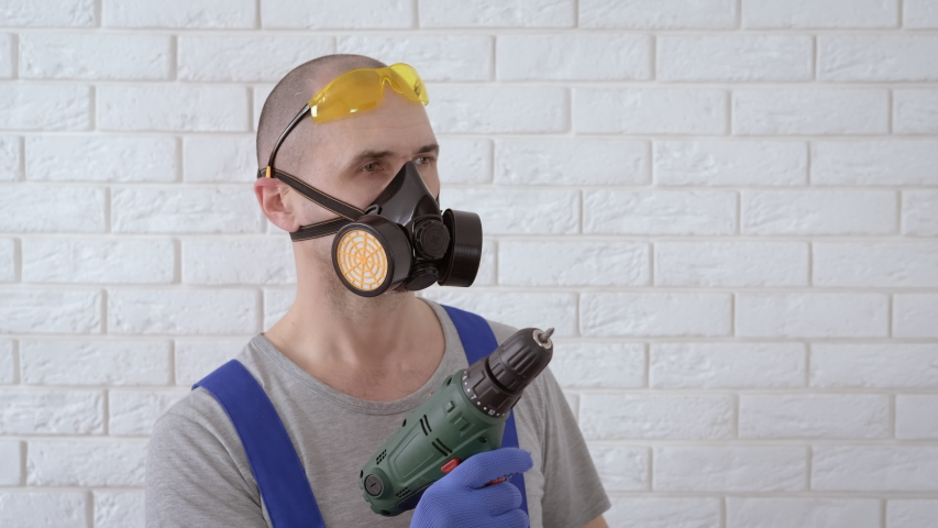 Builder in respirator and goggles | Shutterstock HD Video #1057405351