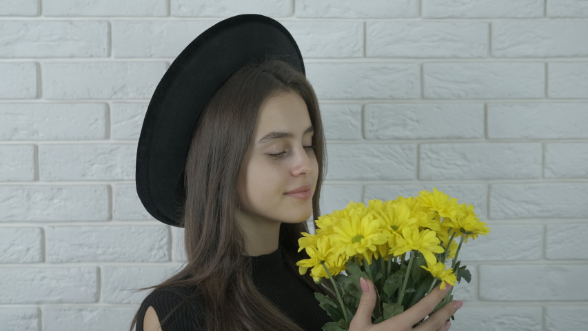Flower like a sun. Nice teen hold a bouquet of flowers of chrysanthemums yellow like a sun in the room. | Shutterstock HD Video #1057405360