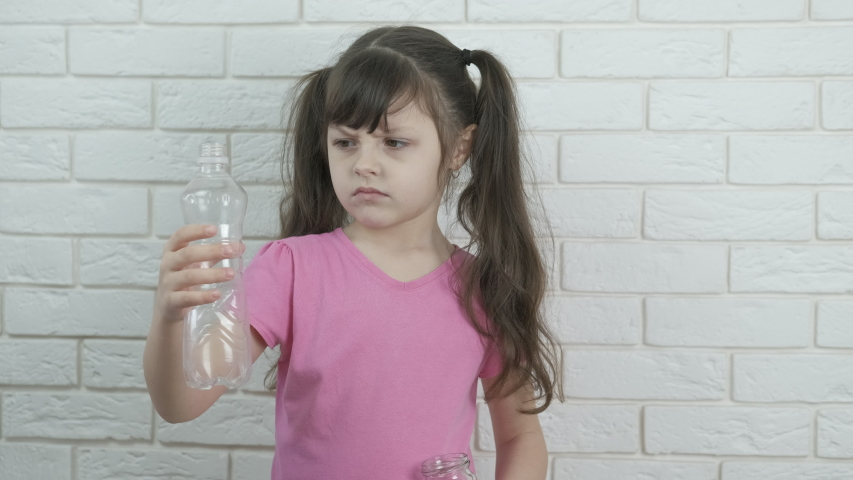Child with an eco bottle. Little girl with a plastic and glass bottle. | Shutterstock HD Video #1057405375