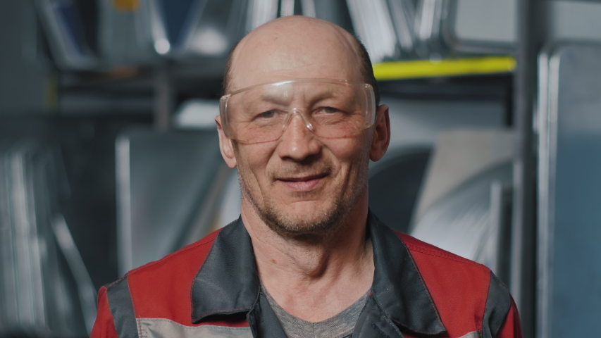 Portrait of a professional engineer in goggles and uniform. Caucasian working man. Confident elderly contractor, welder or car inspection mechanic on the job. | Shutterstock HD Video #1057405414