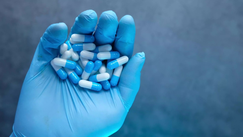 Top view of man hand in protective gloves holding capsules.  | Shutterstock HD Video #1057405615