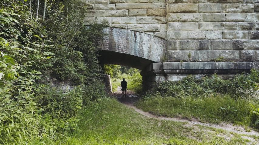 Countryside walk beneath an old bridge  | Shutterstock HD Video #1057405846