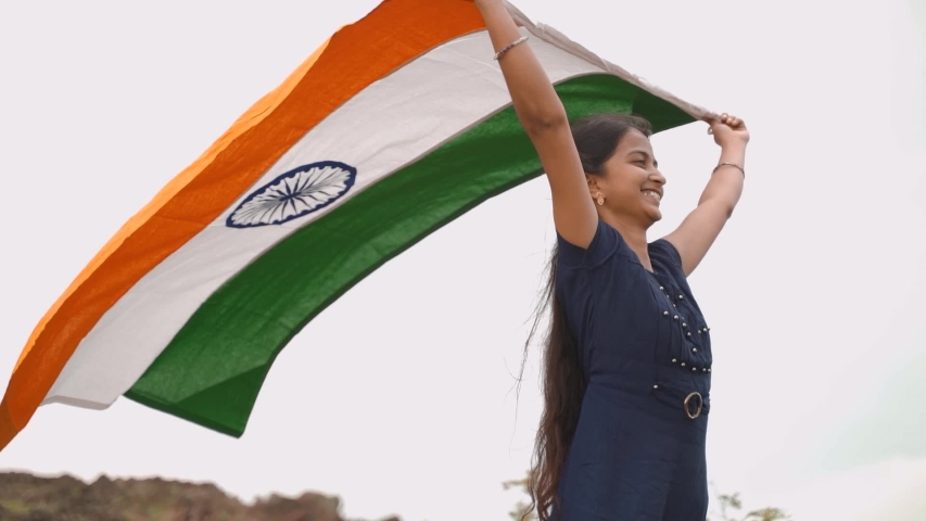 Smiling young Indian Girl proudly waving Holding Indian flag on top of mountain peak in air - Concept of Independence or republic day celebrations or patriotism. | Shutterstock HD Video #1057405999