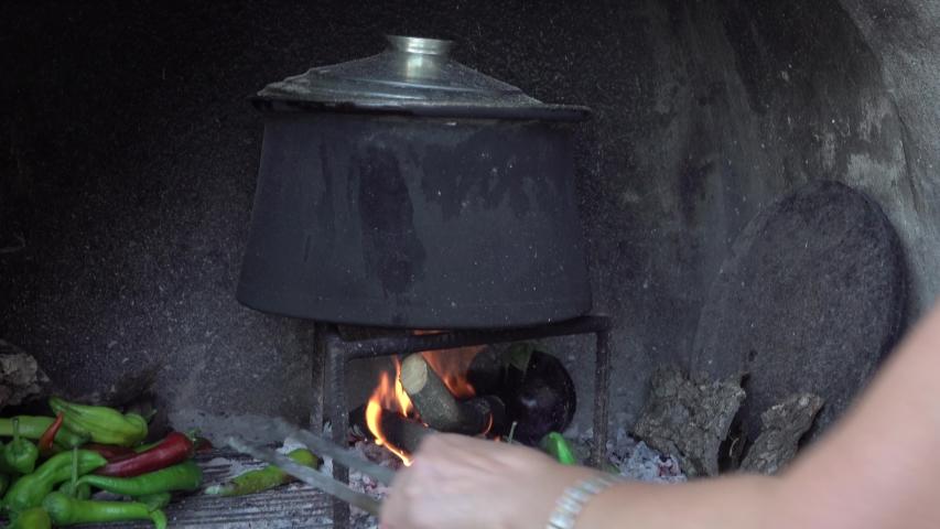 Woman Cooks on Wood Fire   Shutterstock HD Video #1057406656