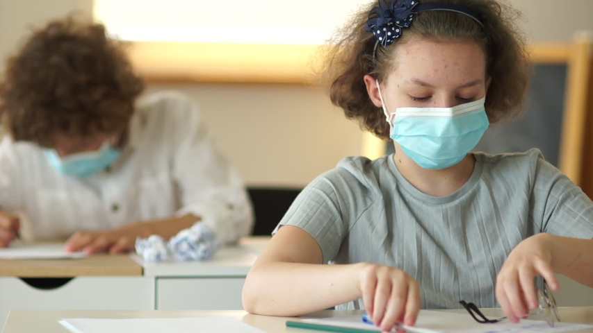 Curly schoolgirl wears glasses. Kids face mask. Back to school covid. Children in protective medical masks sit at their desks at school | Shutterstock HD Video #1057406671