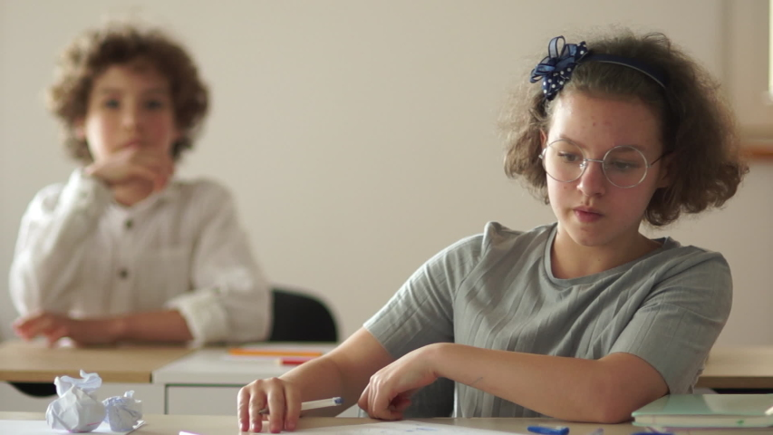 Classmates, a boy and a girl are sitting at their desks during the lesson. Back to school, new school year | Shutterstock HD Video #1057406677