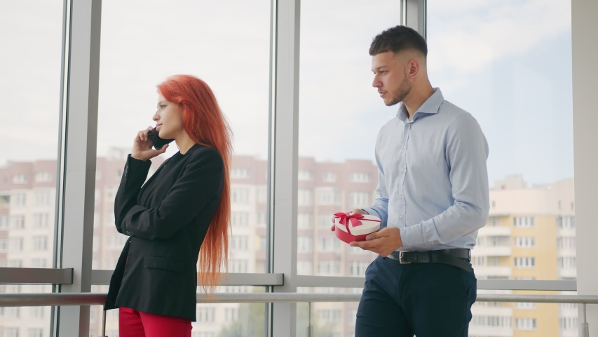 A man gives a gift to a woman with red hair. A woman who speaks on the phone receives a gift from her husband and rejoices at the gift received in the office. | Shutterstock HD Video #1057407250