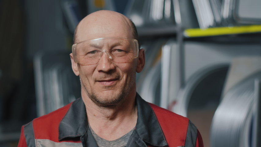 Portrait of a professional engineer in goggles and uniform. Caucasian working man. Craftsman, welder or mechanic at work. | Shutterstock HD Video #1057407598