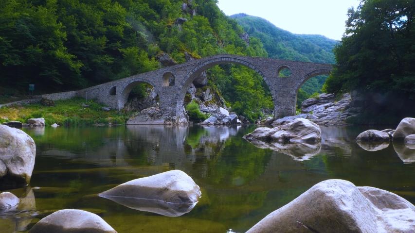 Devil's Bridge in Arda river. Ancient stone bridge over mountain river. Kardzhali Region, Bulgaria, Balkans, Rhodope mountains. | Shutterstock HD Video #1057407604