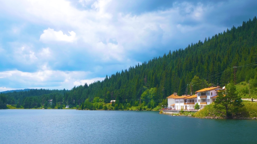 Luxury hotel by the forest mountain lake with crystal clear green water and perfect blue sky in pine forest. Summer vacation in the mountains. Balkans, Bulgaria, Rhodope mountains. | Shutterstock HD Video #1057407607