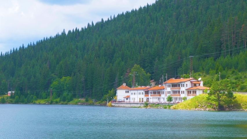Luxury hotel by the forest mountain lake with crystal clear green water and perfect blue sky in pine forest. Summer vacation in the mountains. Balkans, Bulgaria, Rhodope mountains. | Shutterstock HD Video #1057407610