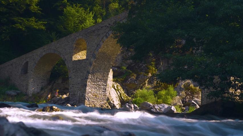 Devil's Bridge in Arda river. Ancient stone bridge over mountain river. Kardzhali Region, Bulgaria, Balkans, Rhodope mountains. | Shutterstock HD Video #1057407613