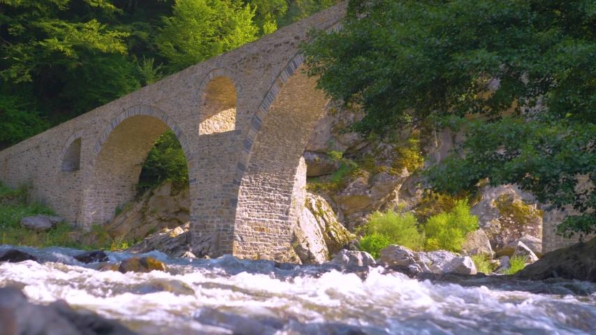 Devil's Bridge in Arda river. Ancient stone bridge over mountain river. Kardzhali Region, Bulgaria, Balkans, Rhodope mountains. | Shutterstock HD Video #1057407622