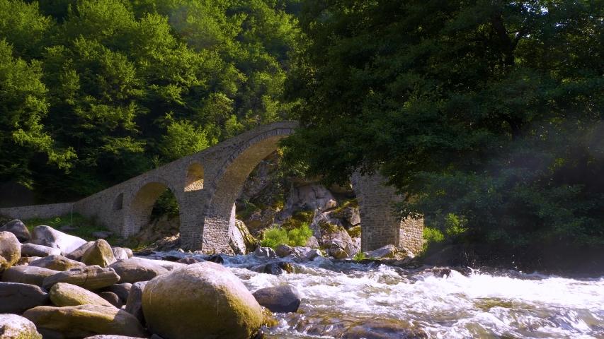 Devil's Bridge in Arda river. Ancient stone bridge over mountain river. Kardzhali Region, Bulgaria, Balkans, Rhodope mountains. | Shutterstock HD Video #1057407628